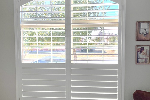 Red interior plantation shutters with 2 chairs