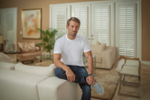 man sitting in living room with shutters